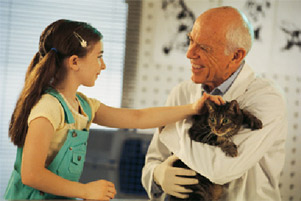 Little girl petting cat in veterinarian's arms